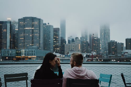 Couple Sitting on Black Chair Looking at City Buildings