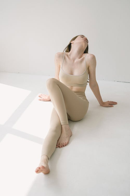 Graceful young slim lady recreating on floor after training