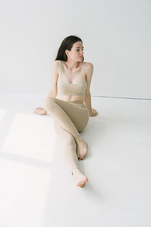 Relaxed slim female sitting on floor in studio after yoga session