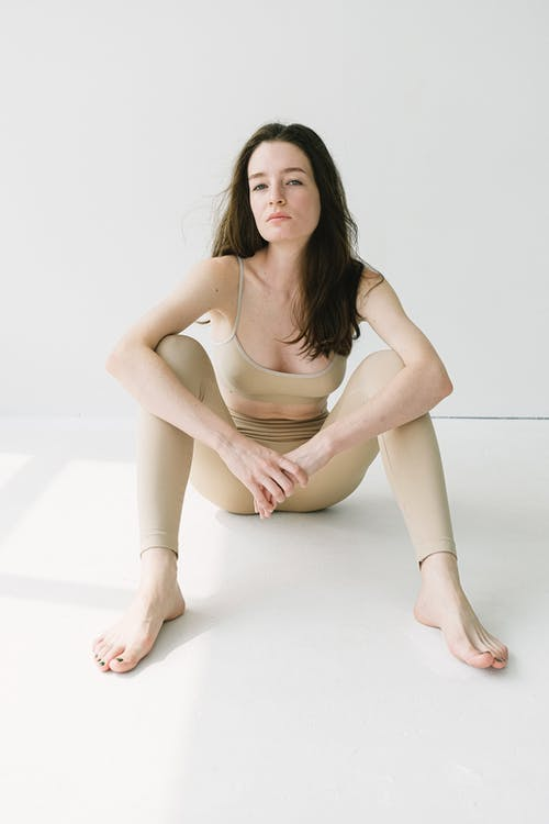 Female with long hair and in beige light sportswear sitting barefoot on studio floor and looking at camera