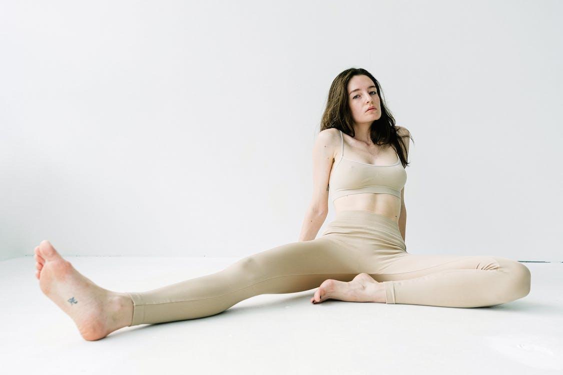 Woman in beige tight activewear in studio