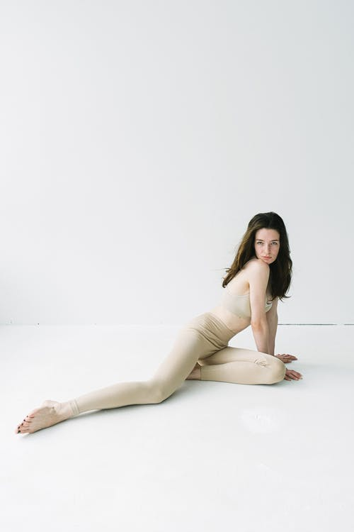 Woman in beige elastic gym suit looking at camera resting chin on shoulder and outstretching leg in studio