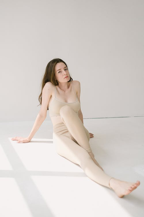 Female in beige activewear looking at camera while sitting on floor leaning on hands behind back in sunlight