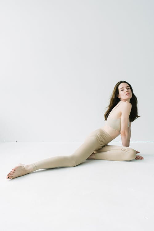 Sporty female in beige sportive clothes with head thrown back and outstretched leg looking at camera against light studio background