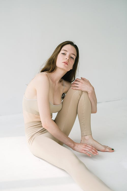 Serious barefoot female with long hair in leggings looking at camera while sitting with bent leg near white wall in light studio