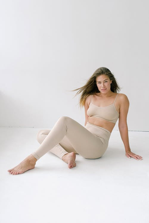 Relaxed woman in leggings sitting near white wall