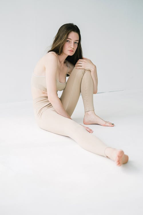 Calm natural woman sitting with bent leg
