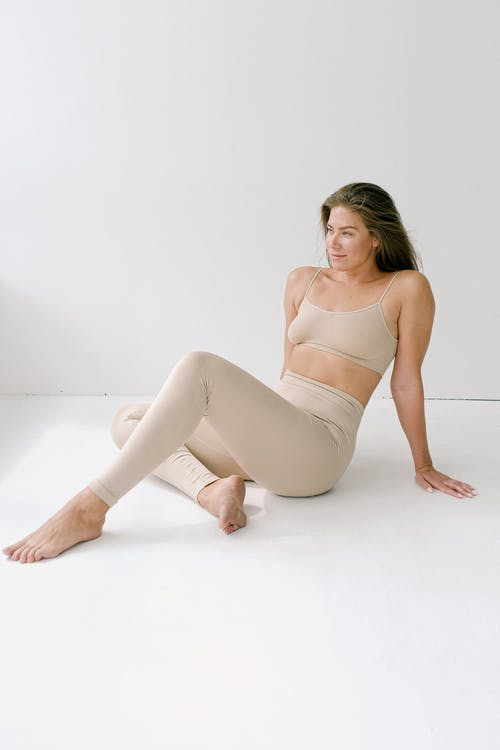 Full body of barefoot slender female wearing top and leggings sitting on floor with bent legs and leaning on arms on white background