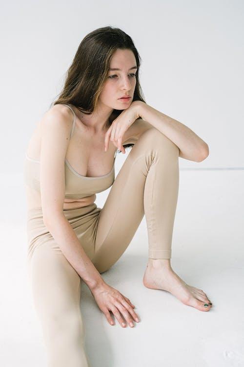 Dreamy slim lady sitting in studio