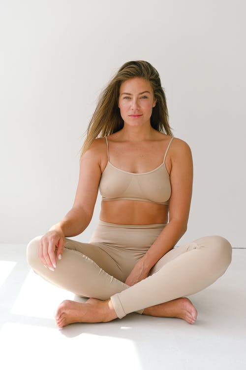 Full body of fit barefoot female with long hair wearing beige activewear looking at camera while sitting in lotus posture against white background