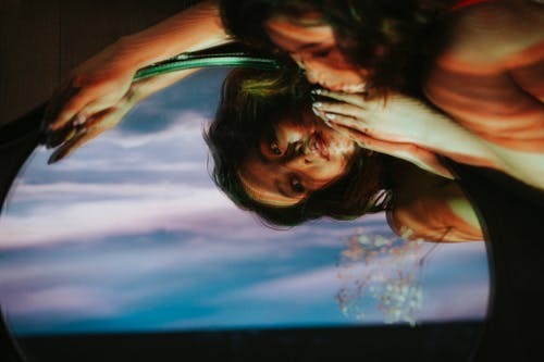 Relaxed Asian female lying on floor with glass mirror with reflection of face and cloudy sky in dark room inside
