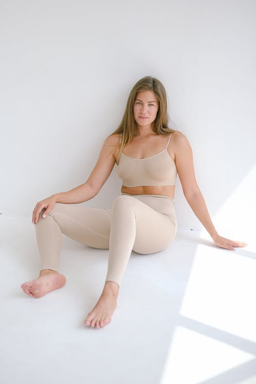 Full body of barefoot slender female wearing beige leggings looking at camera while sitting on floor with bent legs and leaning on wall