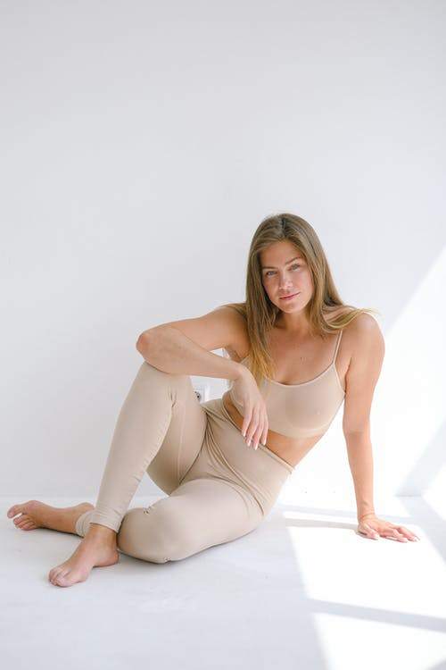 Full body of barefoot female with long hair wearing sportswear looking at camera while sitting with crossed legs and leaning on arm on white background
