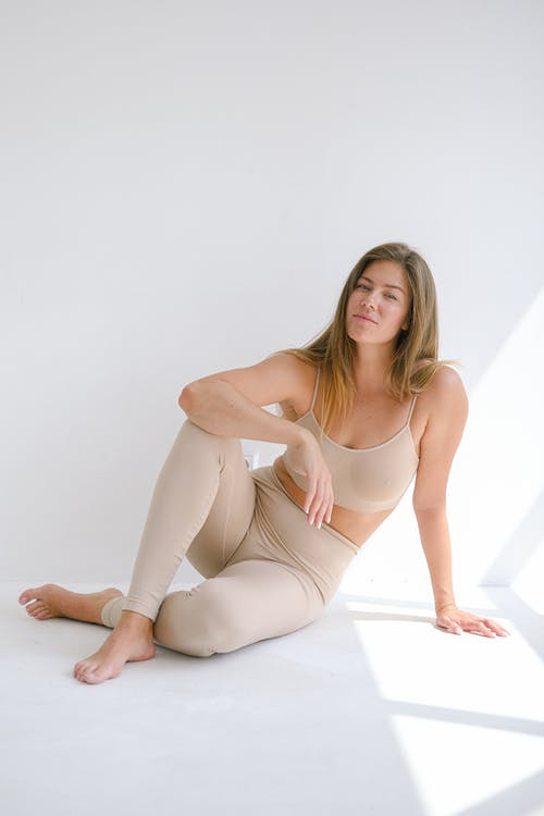 Full body of barefoot relaxed female leaning on arm and looking on camera while sitting on white background with crossed legs