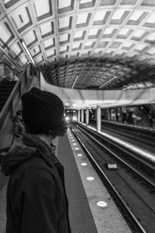 Grayscale Photo of Woman in Black Coat Standing on Train Rail