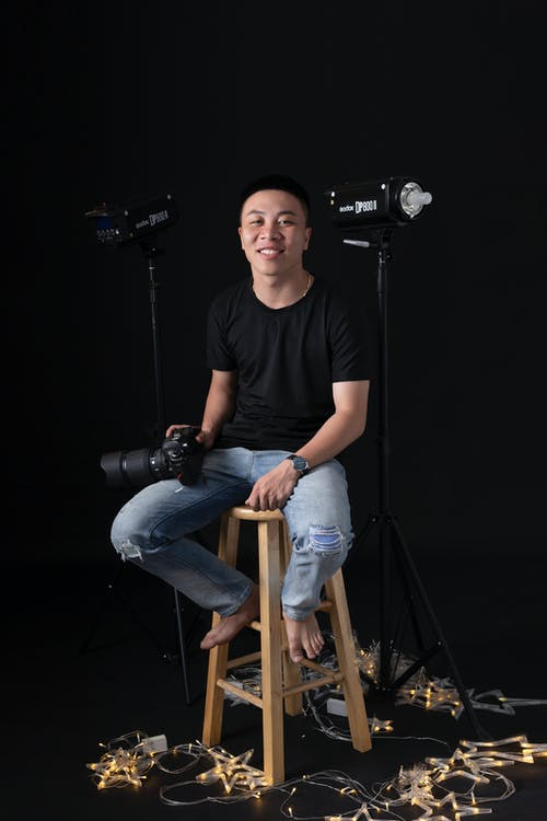 Cheerful ethnic man with camera