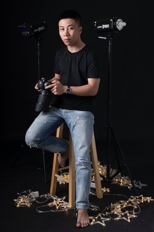 Ethnic photographer sitting on stool