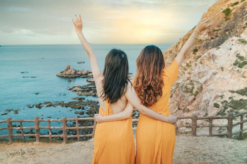 Back view of anonymous female friends in yellow dresses cuddling on rocky cliff while standing with raised arms near calm ocean in summer day