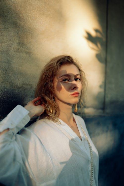 Женщина в белой рубашке в коричневых солнцезащитных очках