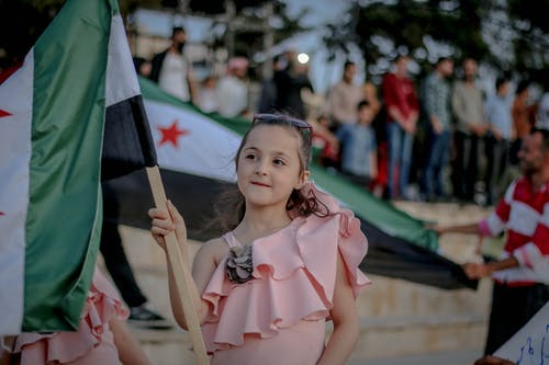 Happy girl in light pink blouse showing unofficial Syrian flag and looking away with smile on protest