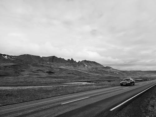 Automobile driving through mountainous countryside on cloudy day