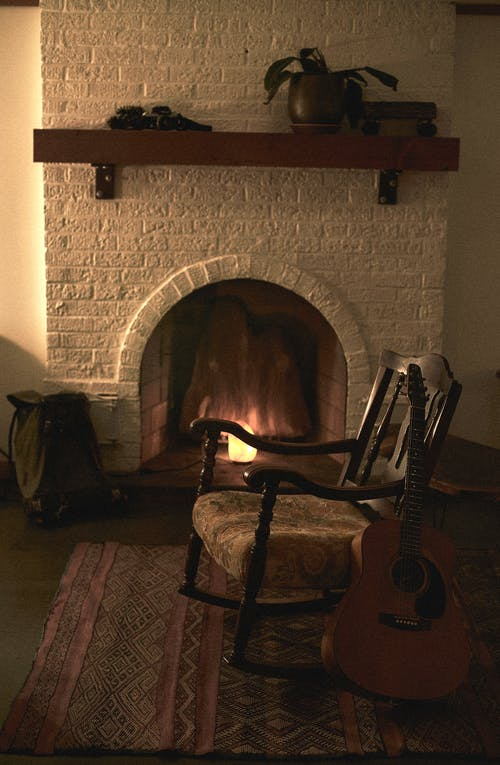 Brown Wooden Rocking Chair Near Fireplace