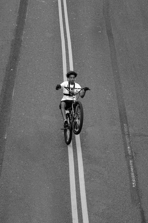 Grayscale Photo of Man Riding Motorcycle on Road