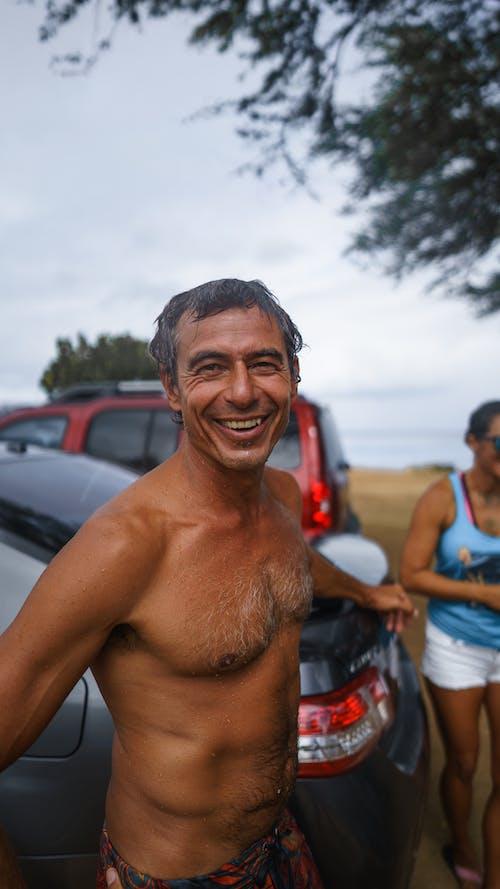 Cheerful happy tanned man near car