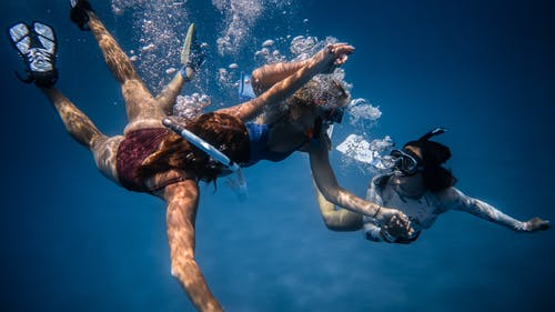 Cheerful people swimming in masks underwater