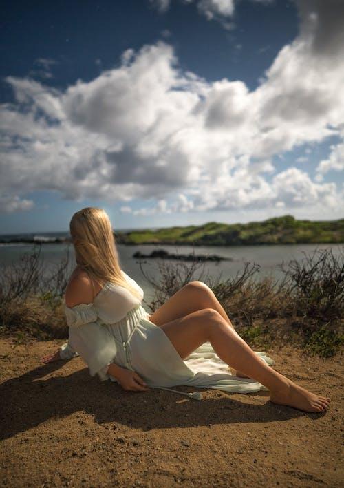 Woman in white silky dress lying on sandy coast