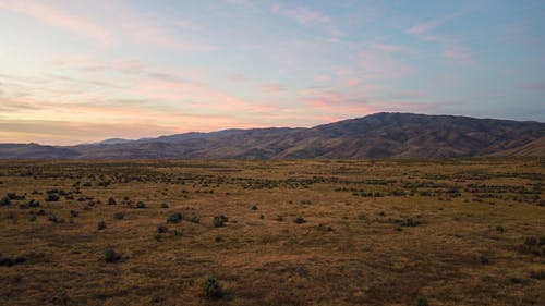 Brown Grass Field Near Brown Mountains Under White Clouds