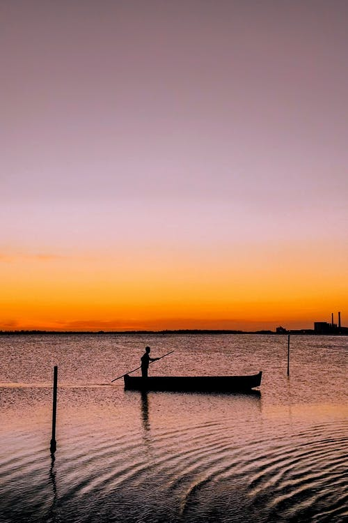 Side view of person standing in boat and floating on calm river at sunset