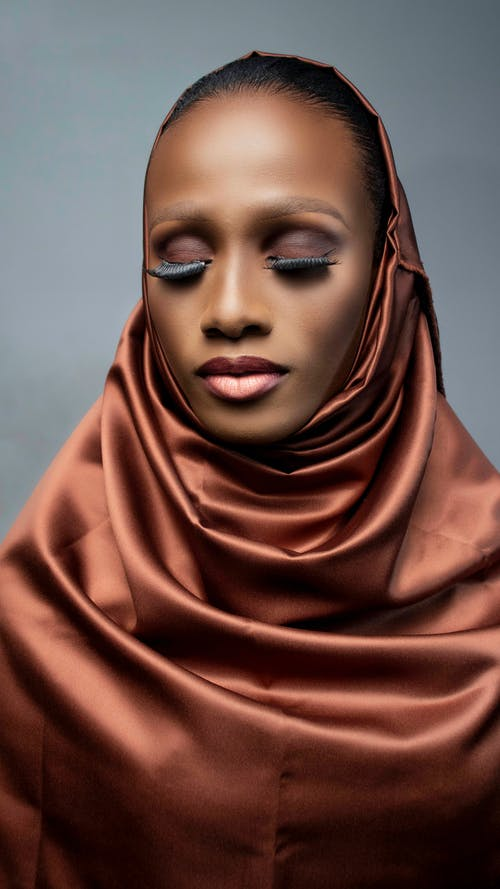 Young stylish African American female in satin headscarf and bright lipstick on gray background
