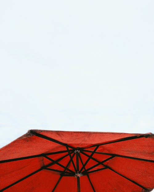 Low angle of bright red umbrella using during summer holidays on hot sunny day