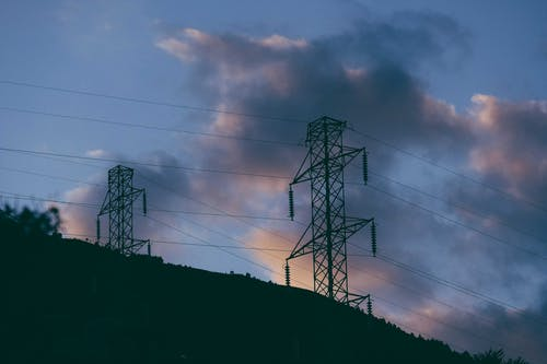 Electricity poles with cables located on hill at sundown