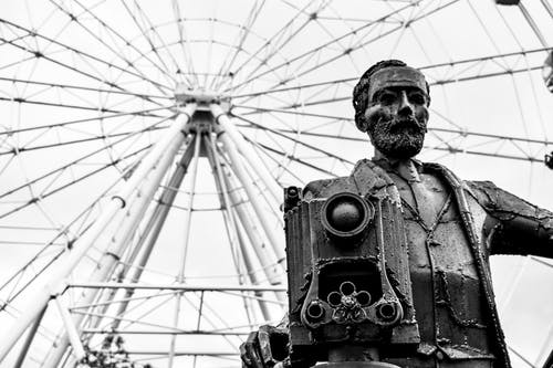Grayscale Photo of Man Holding Camera Statue