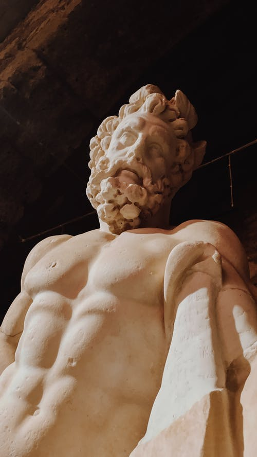 From below of relief statue of Zeus with naked torso against dark background