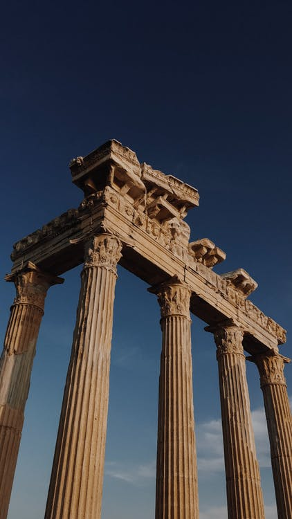 From below of ancient columns left over from large antique building against cloudless blue sky