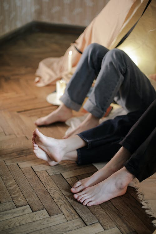 Person in Black Pants and White Socks Sitting on Brown Wooden Floor