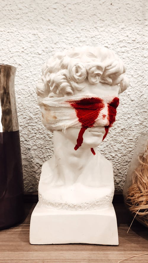 Decorative bust sculpture with bandaged eyes and flowing bloodshot on wooden surface against white wall