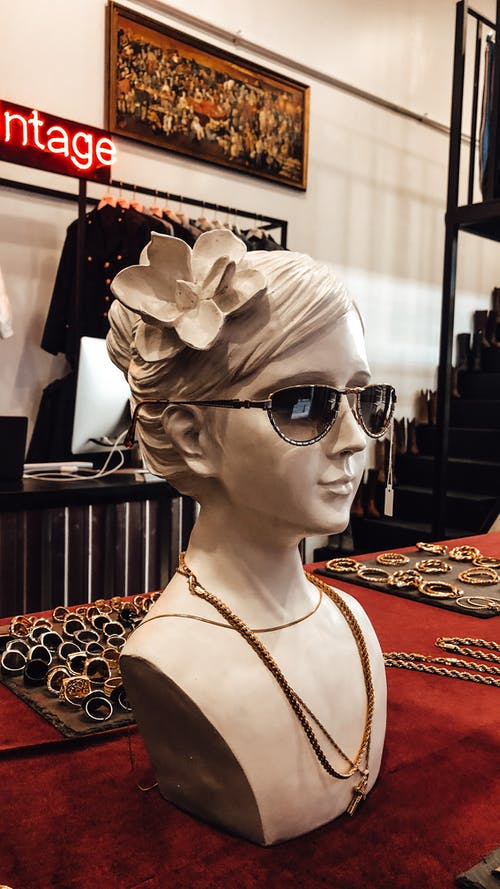 Bust sculpture of female in sunglasses and accessories placed on counter in vintage shop
