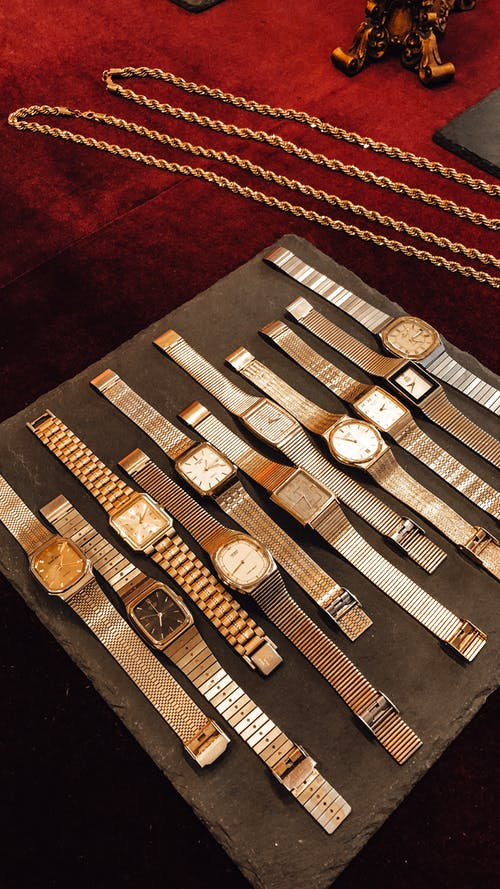 From above collection of vintage golden wrist watches placed on counter in shop