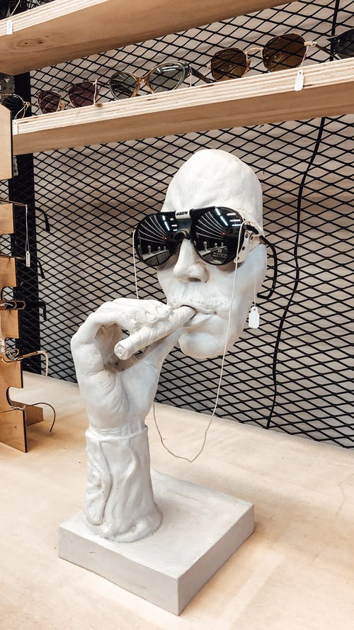 Decorative sculpture in shape of person face with cigar in black sunglasses placed in wooden counter in stylish shop