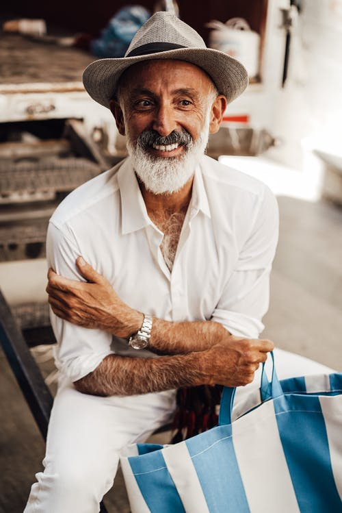 Smiling senior man with tote bag sitting on street
