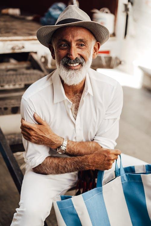 Улыбающийся старший мужчина с большой сумкой, сидя на улице