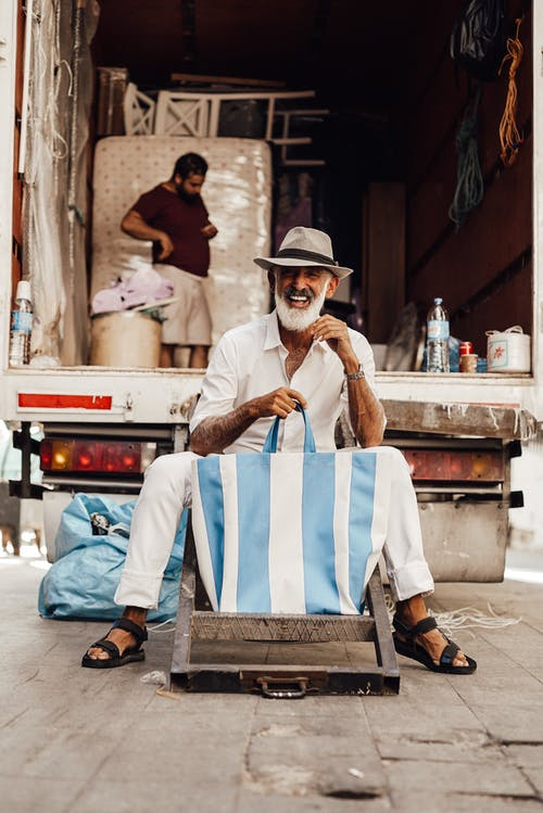 Smiling senior man with white beard in trendy clothes and hat sitting on metal stairs of opened small truck and showing striped tote bag