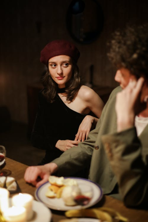 Woman in Black Tank Top and Red Knit Cap Sitting Beside Man in Gray Dress Shirt