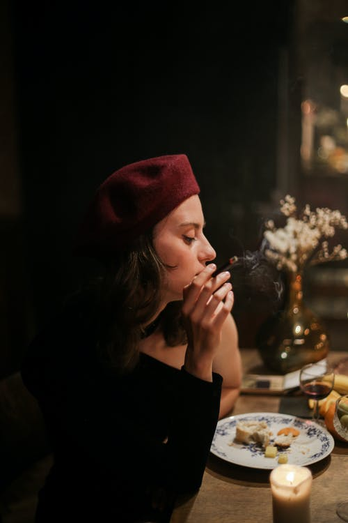 Woman in Black Long Sleeve Shirt and Red Knit Cap Sitting by the Table