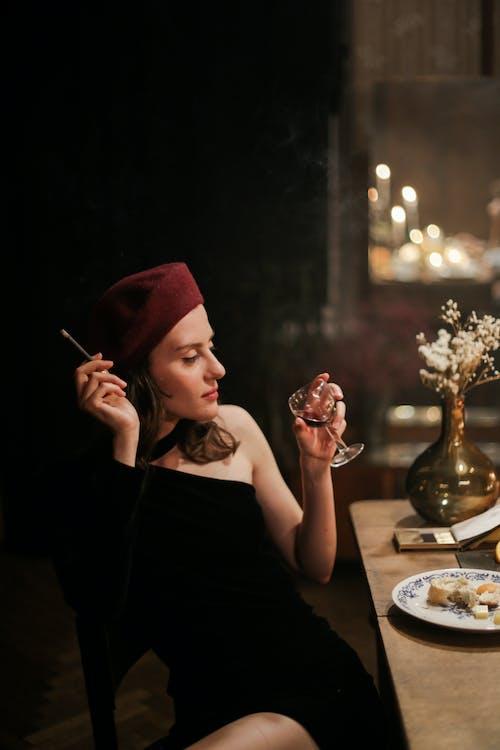 Woman in Black Sleeveless Dress Holding White Cigarette Stick