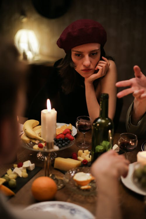 Woman in Black Tank Top Wearing Red Hat Sitting Beside Table With Bottles and Candles